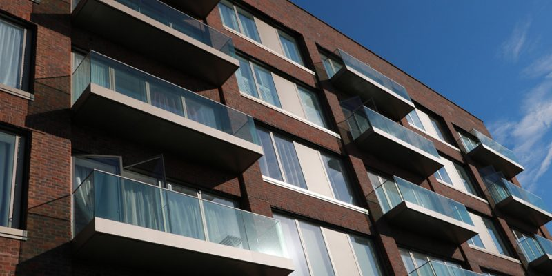 Red brick building with light anodised balcony fascias and soffits