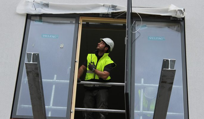 Staines Road balcony - construction worker in hivis PPE awaits balcony