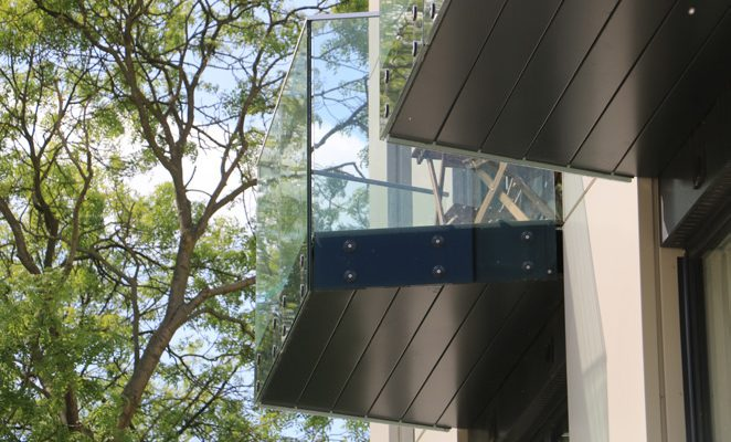 Side draining soffits coated to match printed fascia of glass balcony balustrades